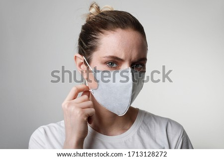 Close-up portrait of young woman in medical face protection mask indoors on white background. Protection of the virus. #1713128272