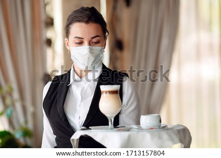 A female Waiter of European appearance in a medical mask serves Latte coffee #1713157804