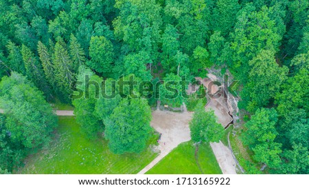 Beautiful aerial view photo from drone on Gutmanala ancient cult site and protected geological feature: sandstone grota cave with inscriptions on its walls, Gauja National Park,Sigulda,Latvia (series)
