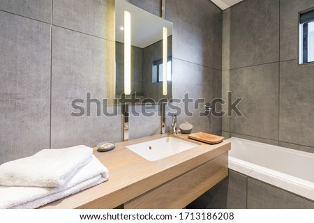 Very stylish and modern bathroom with dark stone walls, back lit mirror, faucet and bathtub Royalty-Free Stock Photo #1713186208