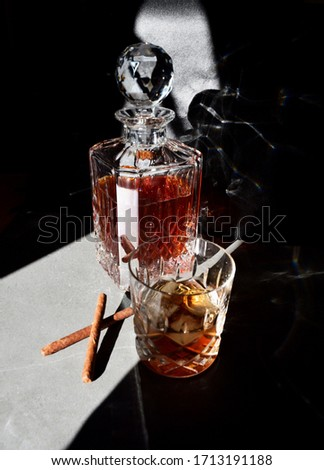 Dark and moody picture of a whiskey in a crystal decanter, glass and cigars. for whiskey and cigar lovers. Poster size picture.