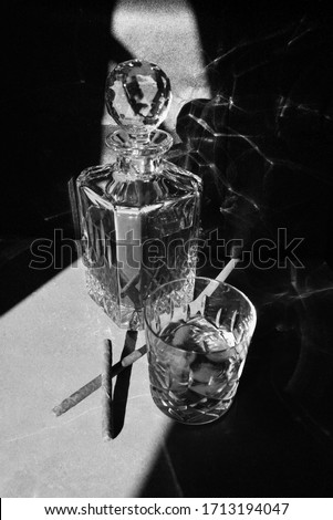 Black and white dark and moody picture of a whiskey in a crystal decanter, glass and cigars. for whiskey and cigar lovers. Poster size picture.
