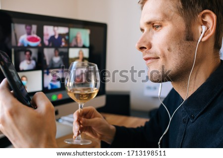 Video conference party online meeting with friends and family. Birthday party in facetime call. Parties during coronavirus quarantine Long Distance Celebration. Glass of white wine in holding hand. #1713198511