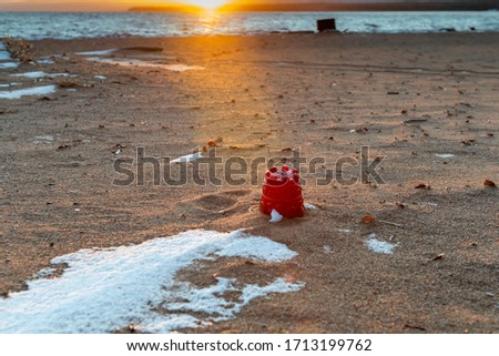A round red sandcastle bucket bottom up on a beach. The sand has seaweed scattered among the sand. There is white snow in clumps on the beach. The ocean is in the background with the sun setting. #1713199762