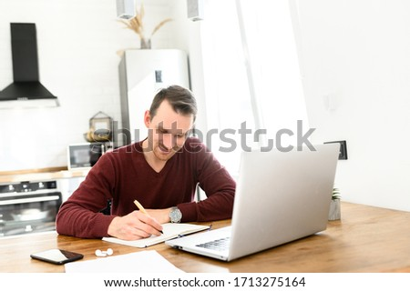 Male student writes a lecture in a notebook at home. He uses a laptop to watch a lecture. #1713275164