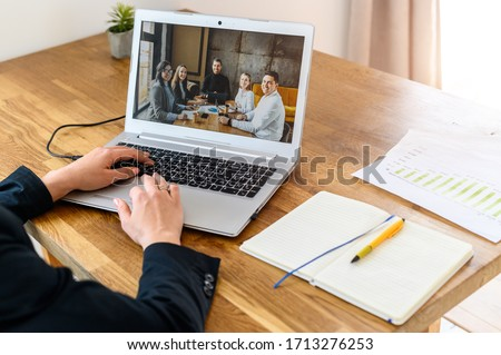 Online meeting. Female hands on the laptop keyboard, group of people on the screen #1713276253