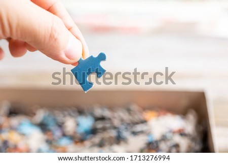 A view of a hand holding a blue colored puzzle piece above a cardboard box full of pieces.