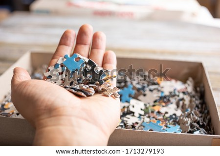 A view of a hand holding a pile of puzzle pieces over the puzzle box full of the rest of the pieces.