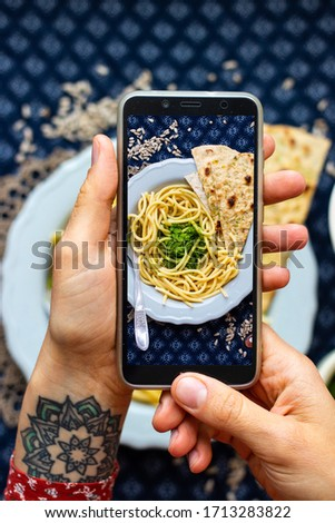 Create blogging content, make phone food photo of vegan lunch. Smartphone meal picture of Italian pasta spaghetti with pesto spread.