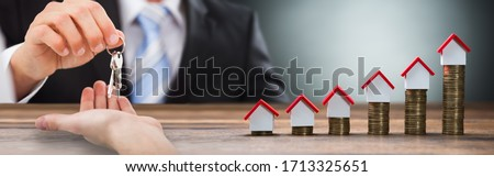Estate Agent Giving House Keys To Man Royalty-Free Stock Photo #1713325651