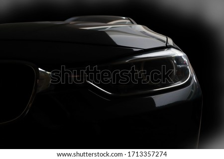 Black modern car headlights - front view with black background in the garage #1713357274