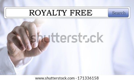Close-up of a hand pressing with the finger on the words 'royalty free' written in the search bar of a virtual screen, with copy space