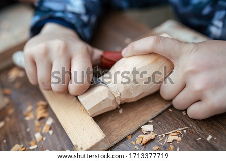 child carves a toy in wood with a knife.  carpenter in the workshop. Close-up of hands  Royalty-Free Stock Photo #1713377719