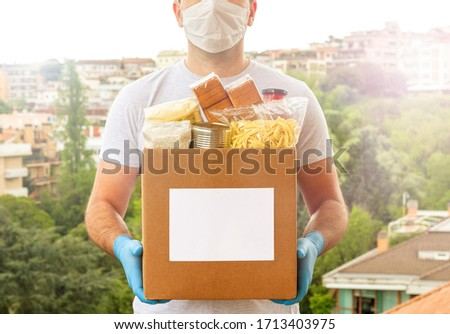 Coronavirus Donation box. Delivery food. Volunteer. Food help. A man in a mask and medical gloves holds a box of food on the street. Coronavirus volunteer. Quarantine  #1713403975