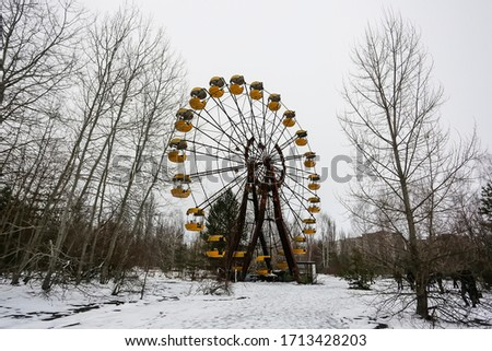 Abandoned amusement park in ghost town Prypiat. Overgrown trees and collapsing buildings in Priryat, Chornobyl exclusion zone. December 2016 #1713428203