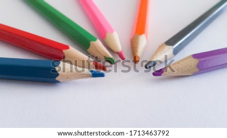 Color pencils pointing towards the center in white background #1713463792