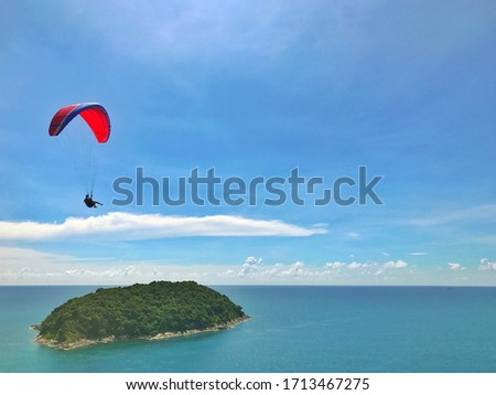 Paraglider in the blue sky. The sportsman flying on a paraglider. #1713467275