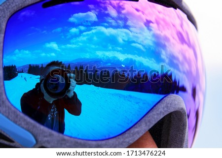 Photographer and camera reflected in glasses in winter with snow and mountains. Outdoor self picture close to the forest, on ski and snowboarding break