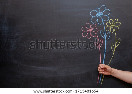 A man's hand holds flowers drawn on a chalkboard in his hand. #1713481654