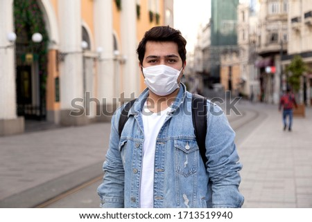 Young man is walking on the street with a protective mask #1713519940
