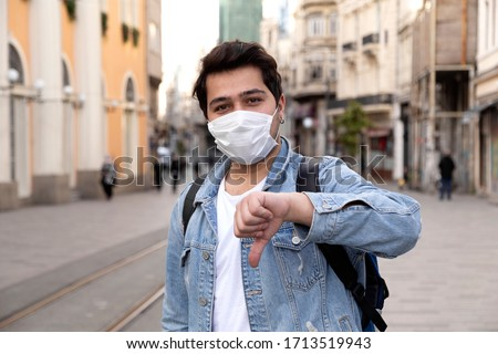 Young man is walking on the street with a protective mask #1713519943