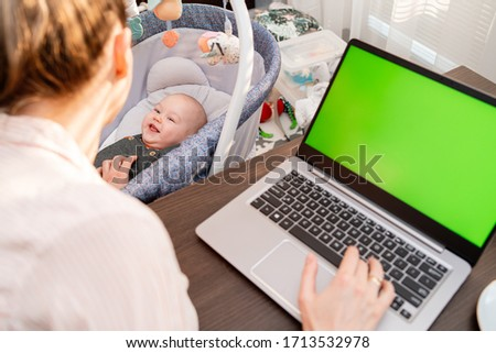 Young mom shopping online on clothing website using laptop. Woman searching for apparel on-line. Son and mummy working from home. Boy playing on the background. Close-up. Back view. Focus on baby. #1713532978