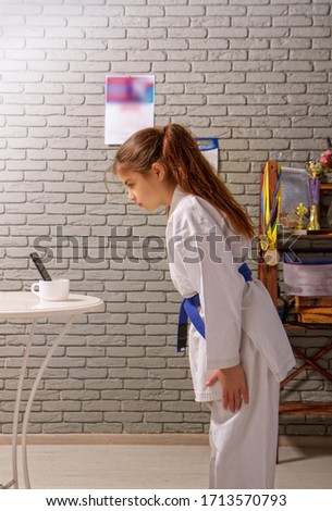 A little girl in a white kimono with a blue belt takes karate lessons via the Internet while at home on self-isolation during quarantine #1713570793