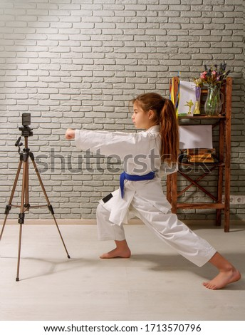 A little girl in a white kimono with a blue belt takes karate lessons via the Internet while at home on self-isolation during quarantine #1713570796