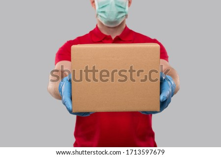 Delivery Man Wearing Medical Mask and Gloves with Box in Hands. Red Tshirt Delivery Boy. Home Delivery. Quarantine Hero. Box Close Up #1713597679