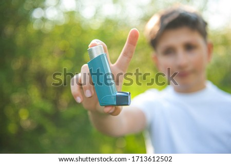 Asthma worl day. A guy has an asthmatic agent in his hands   in the park backgrounds. The boy  in the white T-shirt with asthma inhaler. Royalty-Free Stock Photo #1713612502