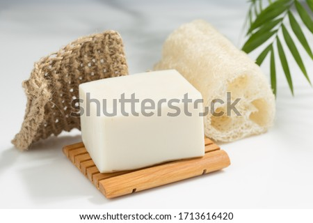 Natural Plant Based Solid Soap Bar on wooden Soap Dish with Knit Twine Scrubber and Luffa Sponge Royalty-Free Stock Photo #1713616420