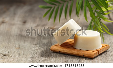Handmade solid shampoo soap bar on wooden dish. Green leaves above and copy space for text. Zero waste, eco friendly product Royalty-Free Stock Photo #1713616438