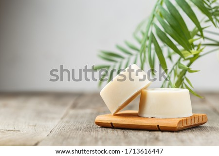 Handmade solid shampoo soap bar on wooden dish. Green leaves above and copy space for text. Zero waste, eco friendly product Royalty-Free Stock Photo #1713616447