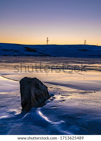 A stone in the middle of the frozen lake Kari at sunset, Armenia. Landscape background #1713625489