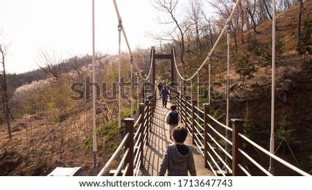 This is a photo of people crossing the shaking bridge at Gyeyangsan Park in Incheon, Korea. #1713647743
