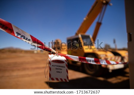 Safe workplace practices red and white warning danger tag tape sign applying taping off working area dropped object with defocused crane lifting high risk work exclusion dropped zone construction site
