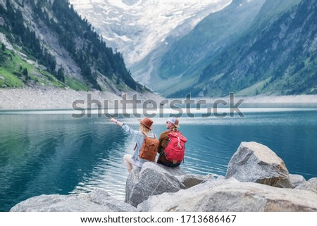 Travel image. Travelers team look on the mountain landscape. Travel and active life concept with team. Adventure and travel in the mountains region in the Austria #1713686467