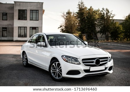 Compact white executive car, with beautiful wheels, large chrome grille. Royalty-Free Stock Photo #1713696460