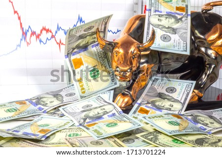 Concept of Financial investment in bull market.  Copper bull near one hundred us dollar bills. Stock market prices chart in background.