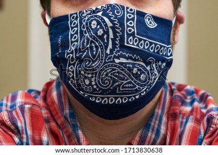 A close up photo of how one wears a homemade, cloth face mask covering the mouth and nose. This mask helps prevent the spread of germs, and it was created during the Coronavirus Pandemic. Royalty-Free Stock Photo #1713830638