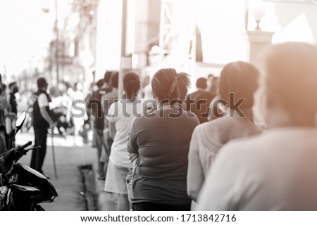 Large group of people waiting in line for Donation charity food.Covid-19 Coronavirus crisis pandemic.Poor crowd of people stand social distancing waiting for grocery and food donation in Thailand. #1713842716
