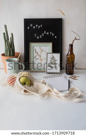 "Cozy and cute styled home work space with inspirational text on black and white letter board. ""Happy thoughts"" words decorate an artistic person's desk. Zero waste, natural and optimistic lifestyle. #1713909718"