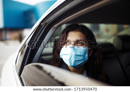 A woman wearing a medical sterile mask in a taxi car on a backseat looking sideway out of open window. Girl passenger waiting in a traffic jam during coronavirus quarantine. Healthcare safety concept #1713950470