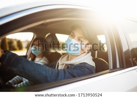 Man driving a car wearing sterile medical mask. Taxi driver with a passanger stuck in a traffic jam during coronavirus quarantine isolation in the city. Prevernt spread of covid-19 concept #1713950524