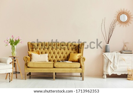 Cozy living room interior of retro armchair, vintage wooden chest dwarf and vintage couch on the background of the beige wall and painted wooden floor #1713962353
