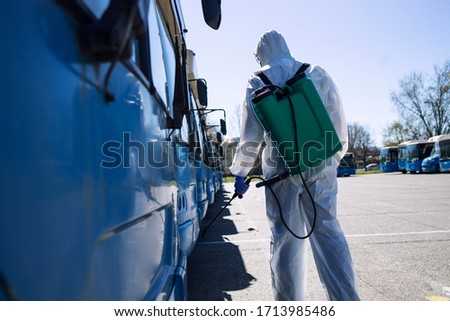 Public transport disinfection. Man in white protective suit with reservoir spraying disinfectant on parked buses. Stop coronavirus or COVID-19. #1713985486