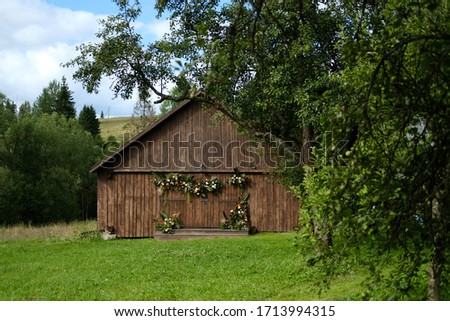 Old barn brown wall wood background surrounded by green trees. The barn is decorated with flowers and greenery. rustic wedding concept .