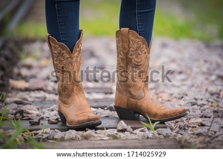 Close-up of tan leather cowboy boots worn by woman next to railroad tracks #1714025929