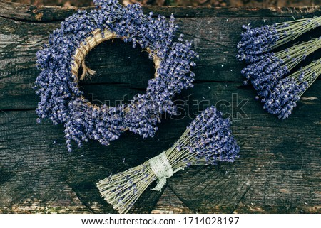 Top view of big handmade lavender wreath and bunches of dried lavender placed on very old wooden texture. Composition of big and small lavender bouquets and round wreath. Lavender harvest #1714028197