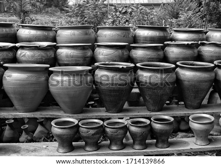 Clay pots stacked for sale on African roads. Pottery making place. Local craft market in Africa. Handmade ceramic pots. Craftsmanship. African style. Black and White Photography.